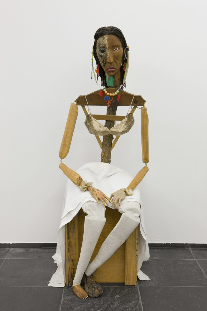 Jimmie Durham, Malinche, 1988-1992. Guava, pine branches, oak, snakeskin, polyester bra soaked in acrylic resin and painted gold, watercolor, cactus leaf, canvas, cotton cloth, metal, rope, feathers, plastic jewelry, glass eye. 70 × 23 ⅝ × 35 in. (177 × 60 × 89 cm). Stedelijk Museum voor Actuele Kunst (SMAK), Ghent, Belgium. Image ©S.M.A.K. / Dirk Pauwels.