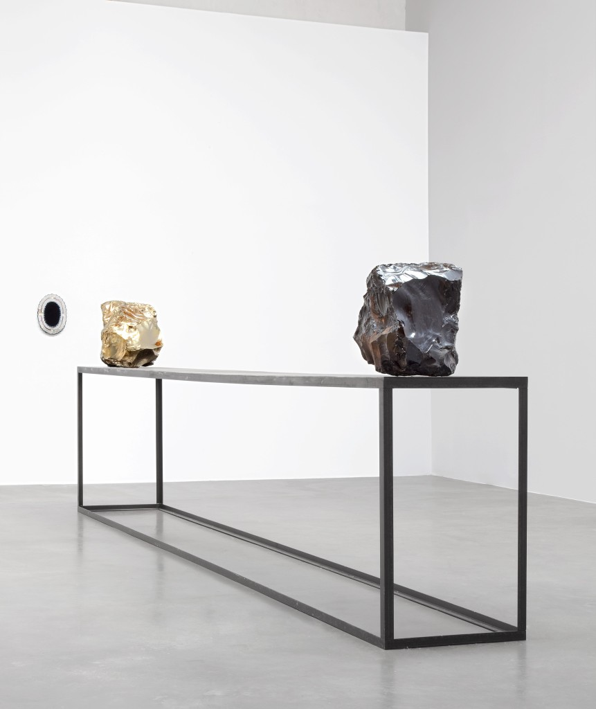 Jimmie Durham, Upon reflection, I was no longer sure of my position, 2009. Obsidian, German silver (copper, zinc, and nickel), steel table, obsidian mirror with colored tin frame. Mirror: 13 ½ × 10 × ¾ in. (34 × 25 × 2 cm); table: 39 ½ × 197 × 23 ½ in. (100 × 500 x 60 cm); obsidian: 18 ½ in. (47 cm) diameter; German silver: 17 ¾ in. (45 cm) diameter. Hammer Museum, Los Angeles. Purchase. Image courtesy of kurimanzutto, Mexico City.