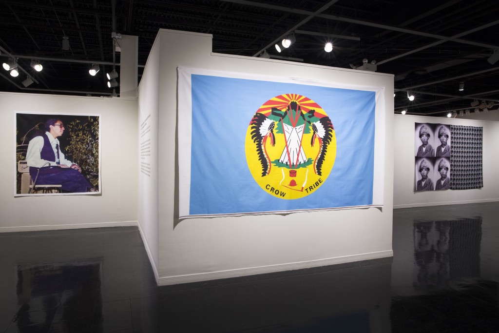 Caption: Image of Wendell Red Star, Crow Nation Flag, and Wallace Red Star, Jr., Wendy Red Star: The Maniacs (We're Not The Best, But We're Better Than The Rest), University Art Gallery, New Mexico State University. Photo Courtesy of Mónica Martínez.